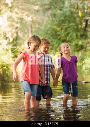 USA, Utah, Lehi, drei Kinder (4-5, 6 und 7) Hand in Hand und gehen gemeinsam in kleinen Bach - Stockfoto