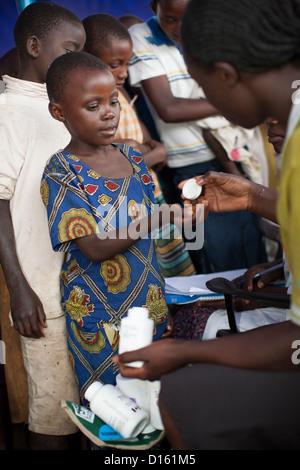 Kinder in die Warteschlange für Entwurmung Medikamente eine Immunisierung Outreach Camp in Kitugutu Dorf, Kyenjojo - Stockfoto