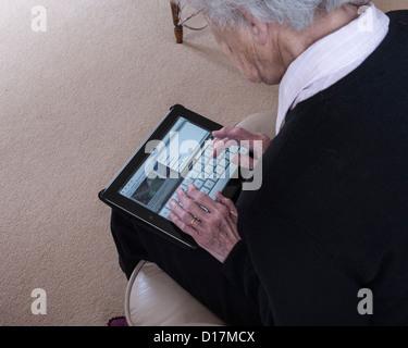 Ältere Dame Tippen auf dem iPad, UK. Europa - Stockfoto