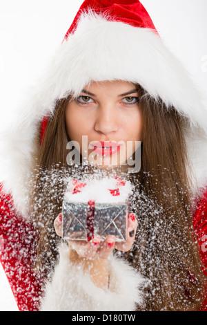Porträt von schönen Santa Mädchen Schneetreiben aus Silber Weihnachts-Geschenk-Box in der Hand. - Stockfoto