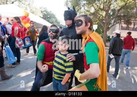 Kleiner Junge Posen mit mehreren Kindern Buchautoren verkleidet in Superhelden-Kostümen einschließlich Batman, Robin - Stockfoto