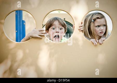 Jungen und Mädchen Grimassen durch Kreise - Stockfoto