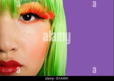 Zugeschnittenes Bild junge Frau trägt falsche Wimpern lila Hintergrund - Stockfoto