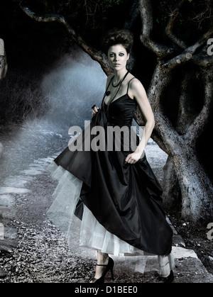 Schöne junge Frau, die klassischen langen schwarzen Kleid in einem dunklen geheimnisvollen Wald. Digital komponierten - Stockfoto
