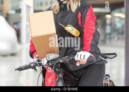 Weibliche Radfahrer mit Karton und Courier Bag auf Straße - Stockfoto