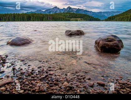 Drei Felsen in einem wellig See mit Wald und Berg-Gipfel in der Ferne. - Stockfoto