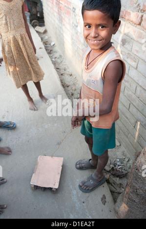 Lächelnde Dorfjunge mit Rädern Spielzeug Fahrzeug zog am Stück Draht in eine Dorfstraße, ländlichen West Bengalen, - Stockfoto