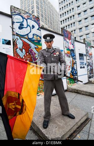 Ostdeutschen Wache mit ehemaligen DDR-Flagge vor der Reste der Berliner Mauer, Potsdamer Platz, Berlin, Deutschland, - Stockfoto