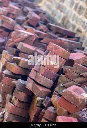 Alte handgemachte Ziegel in Haufen gestapelt gegen Steinmauer - Stockfoto