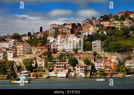 Ringwade Fischerboot am Bosporus mit Häuser auf dem Hügel in Yeni Mahalle Sariyer Türkei - Stockfoto
