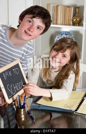 Zwei Jugendliche schreiben zurück zur Schule auf einer kleinen Tafel - Stockfoto