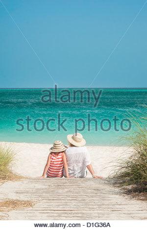 Mutter und Tochter sitzen auf der Promenade mit Blick auf Ozean, Grace Bay Beach, Providenciales, Turks-und Caicosinseln, - Stockfoto