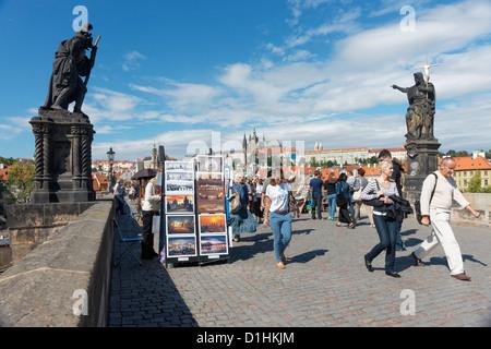 Touristen zu Fuß über die Karlsbrücke, Prag, Tschechische Republik. Statuen sind St. Christopher (L) und St. Johannes - Stockfoto