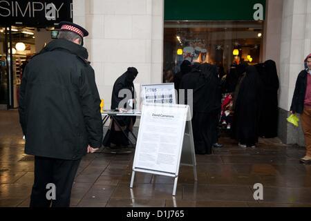 London, UK. 24. Dezember 2012 Polizist liest ein Board Aufmachungen von einer radikalen muslimischen Gruppe. Das - Stockfoto