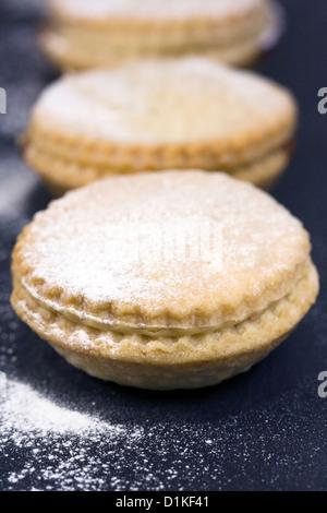 Frisch gebackene Mince Pies auf einer Schiefertafel Platte serviert. - Stockfoto
