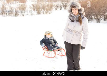 Glückliche attraktive junge Mutter Abschleppen ihres Sohnes auf einem bunten Orange Rodeln an einem kalten Wintertag - Stockfoto