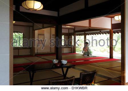 junge Frau im Kimono sitzen und mit Blick in den Garten in einem traditionellen japanischen Haus - Stockfoto