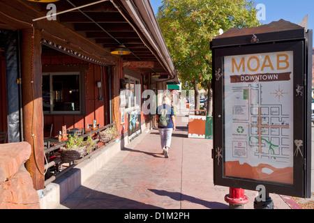Frau zu Fuß entlang der Hauptstraße und Geschäfte in Downtown Moab Haupt Straße Moab Utah Vereinigte Staaten von - Stockfoto