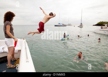 Ein Teenager, der Sprung in das Karibische Meer an einen Familienurlaub, St Lucia, West Indies - Stockfoto