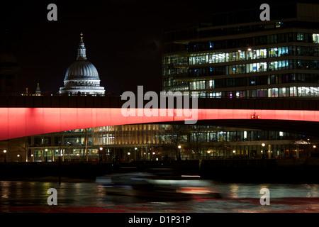 Str. Pauls Kathedrale bei Nacht mit London Bridge leuchtet rot im Vordergrund und ein Boot vorbei, darunter London, - Stockfoto