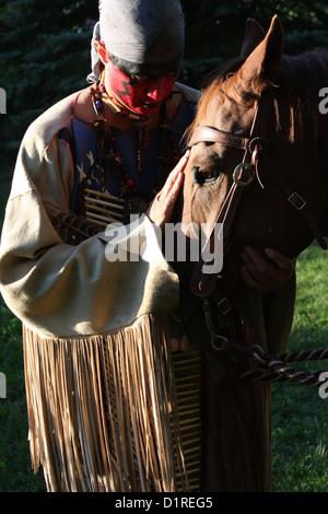 Ein Native American Indian Mann mit roter Bemalung Gruß sein Pferd. - Stockfoto