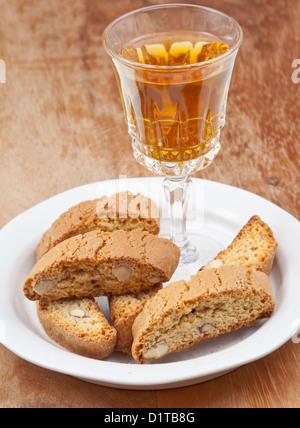 Kristallglas mit Weißwein und italienischer Mandel-Cantuccini auf Untertasse auf Holztisch - Stockfoto