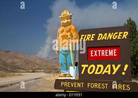 Smokey Bear extreme Feuer Warnschild mit einer Wolke aus Rauch von einem Waldbrand im Hintergrund in Boise County, - Stockfoto