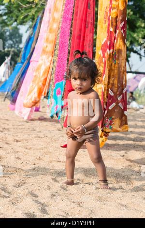 Indische Mädchen spielen im Sand neben Saris auf der Wäscheleine. Andhra Pradesh, Indien - Stockfoto