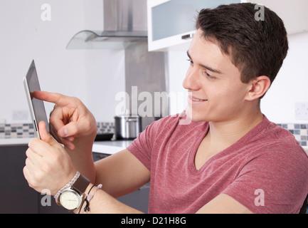 Junger Mann mit einem digitalen Tablet-Bildschirm oder Monitor zu betrachten. Befindet sich in einer modernen Küche. - Stockfoto