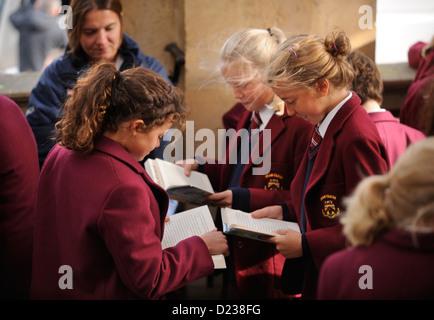 Kinder von Dean Close Preparatory School, Cheltenham im Rathaus zu lesen, während sie warten, Busse nach einem Ereignis - Stockfoto