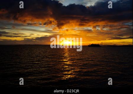 Die untergehende Sonne am flach ruhige Meer in Sorong Raja Ampat West Papua. Dunklen Ozean unter dunklen Wolken - Stockfoto