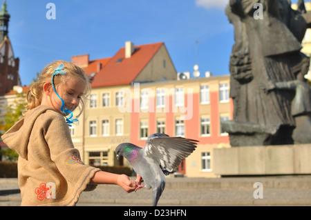 Kleines Mädchen füttert Tauben in der Stadt. - Stockfoto