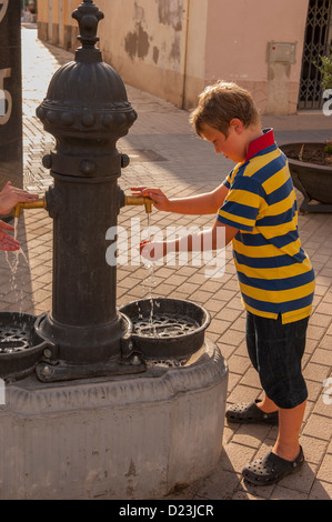 Ein 8-jähriger Junge Trinkwasser aus einem Brunnen in Spanien - Stockfoto