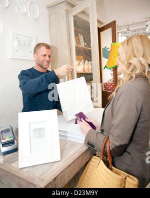 Eine männliche Verkäuferin Übergabe kauft zu einer Kundin - Stockfoto
