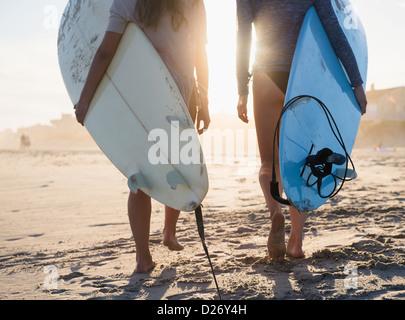 USA, New York State, Rockaway Beach, zwei weibliche Surfer zu Fuß am Strand - Stockfoto