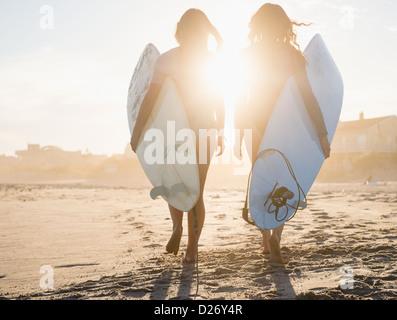 USA, New York State, Rockaway Beach, zwei weibliche Surfer zu Fuß am Strand bei Sonnenuntergang - Stockfoto