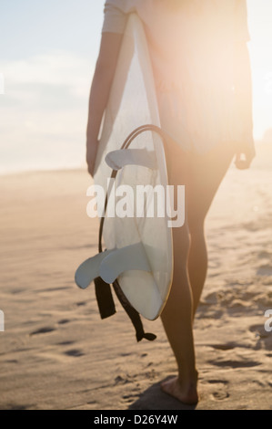 USA, New York State, Rockaway Beach, Surferin zu Fuß am Strand bei Sonnenuntergang - Stockfoto