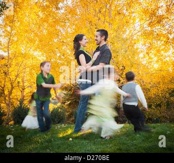 USA, Utah, Bountiful, Familie mit Kindern (2-3, 4-5, 6-7, 8-9) tanzen im Garten im Herbst - Stockfoto
