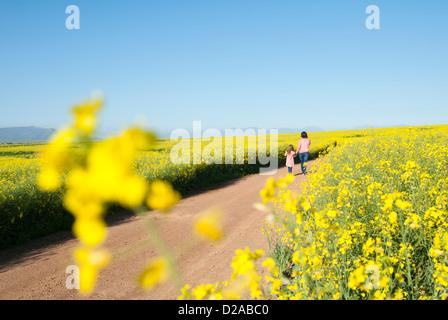 Mutter und Tochter auf Feldweg zu Fuß - Stockfoto