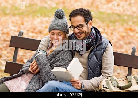Paar Lesung zusammen auf Parkbank - Stockfoto