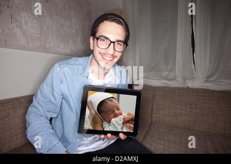 Mann mit Neugeborenen auf dem Tablet PC - Stockfoto
