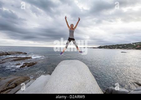 Frau springen vor Freude auf Findling - Stockfoto