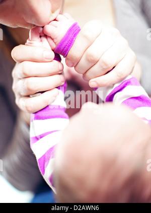 Overhead beschnitten Blick auf eine liebevolle junge Mutter ihr Baby Hände küssen - Stockfoto