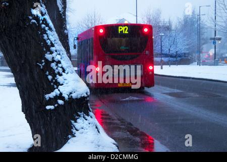 Beleuchtete Bus an einem verschneiten Tag in London - Stockfoto