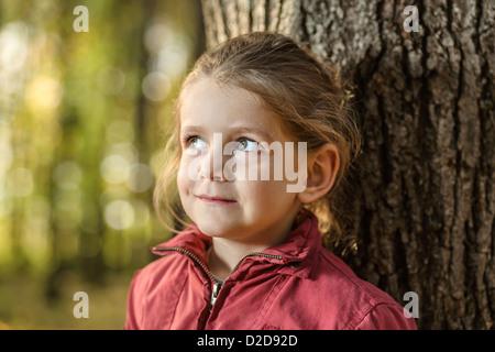 Ein junges Mädchen, neugierig und an einen Baumstamm gelehnt wegschauen - Stockfoto