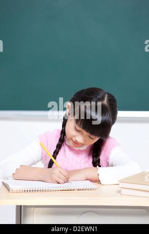 Schönes Schulmädchen schreiben im Klassenzimmer - Stockfoto
