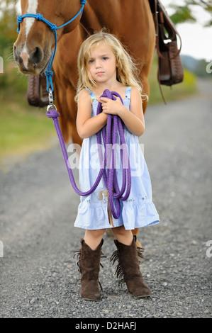 Kleine blonde Mädchen posiert mit ihren großen Pferd auf einen Feldweg, zuversichtlich Pose mit stetigen Blick, - Stockfoto