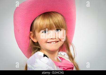 Ziemlich 3-jähriges Mädchen lächelnd und trägt einen rosa farbigen Stil Cowboyhut - Stockfoto