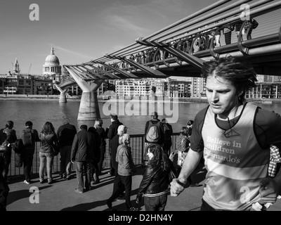 ein junger Mann läuft unter Millennium Bridge an einem sonnigen Tag - Stockfoto