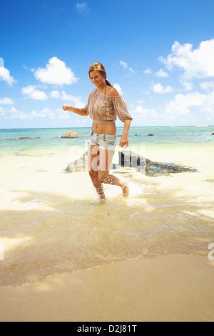 Eine junge Frau läuft im flachen Wasser auf Anini Beach; Kauai Hawaii Vereinigte Staaten von Amerika - Stockfoto